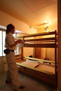 組みあがったベッドに丁寧に養生をする、菅谷現場監督。