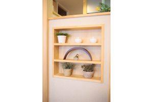キッチンとリビングの境壁ニッチに無垢材を使用した棚取り付け