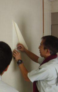場合によってはお客様の許可のもと、壁紙の一部を剥がして壁の構造を確認することもあります。写真の現場では、壁がコンクリートブロックに仕上げ材を貼っていることが分かりました。※ご契約前は住まいを傷つけることは一切行いません。