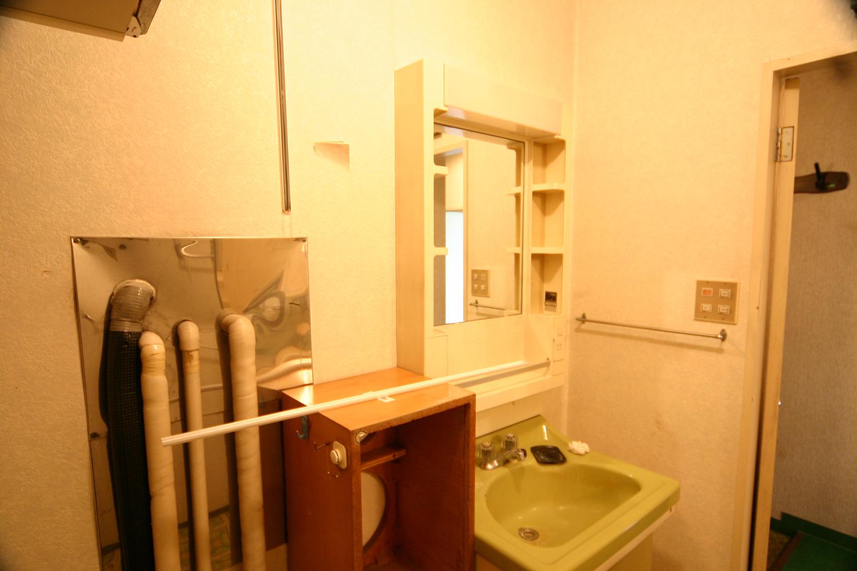 リフォーム前の配管がむき出しの洗面室